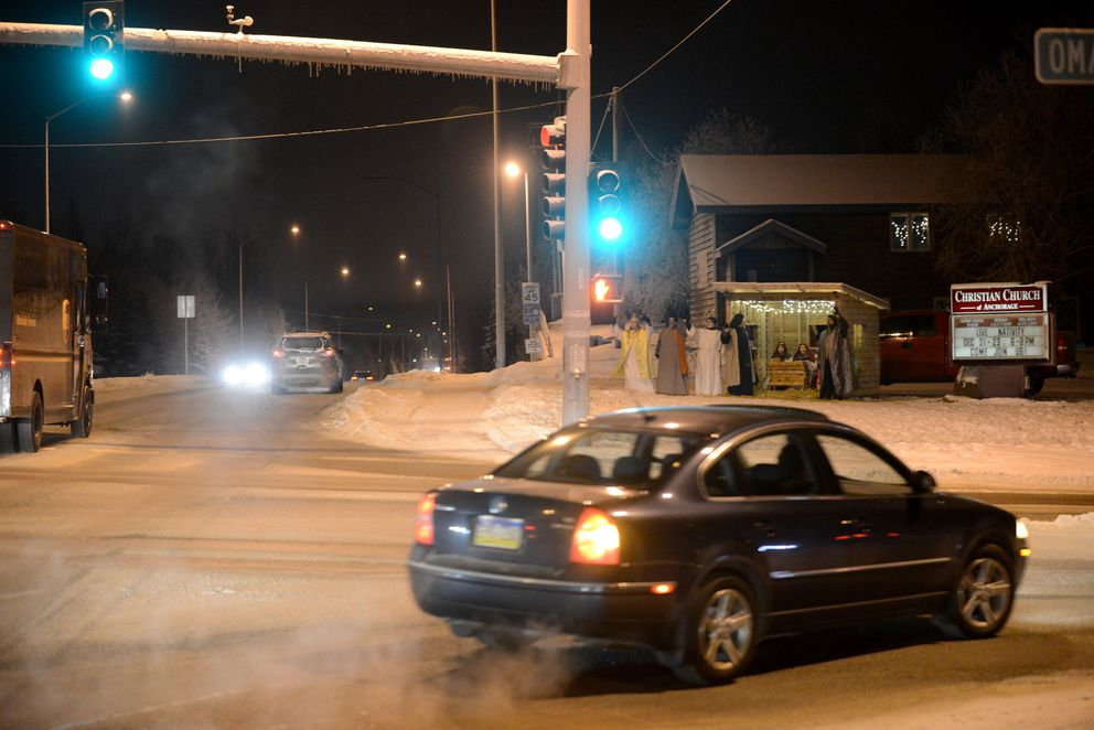 Members of the Christian Church of Anchorage wave to passing cars as they take part in a living Nativity at the church on the corner of Lake Otis Parkway and O'Malley Road. (Bob Hallinen / Alaska Dispatch News)