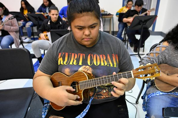 Athalia Eseroma, an East High sophomore, reads her music and plays the ukulele in class on November 20, 2019. (Marc Lester / ADN)