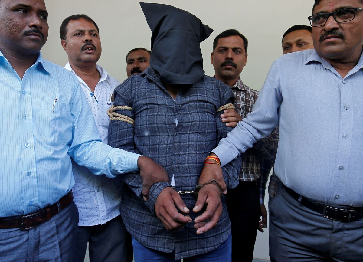 Plainclothes police officers escort Harshsai Gurjar (face covered), who is accused of sexual attack and murder of an 11-year-old girl, to present him before the media at a crime branch office in Ahmedabad, India April 21, 2018. REUTERS/Amit Dave