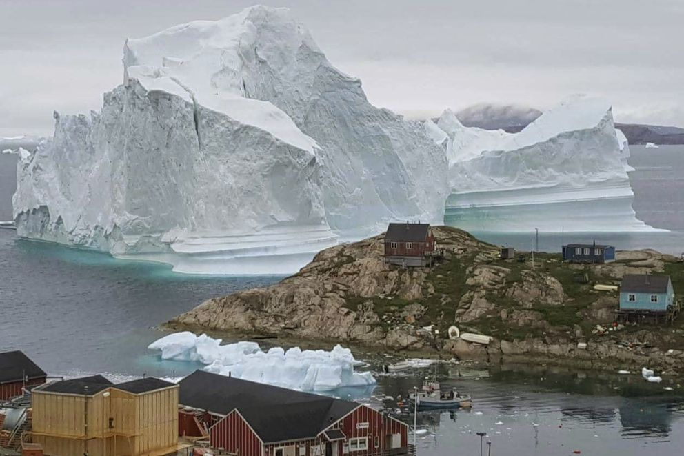 In this Thursday, July 12, 2018 photo, a view of an Iceberg, near the village Innarsuit, on the northwestern Greenlandic coast. Scientists have watched an iceberg four miles long break off from a glacier. The iceberg is allegedly grounded on the sea floor. Residents in houses near the shore are prepared for an evacuation. (Magnus Kristensen/Ritzau Scanpix via AP)