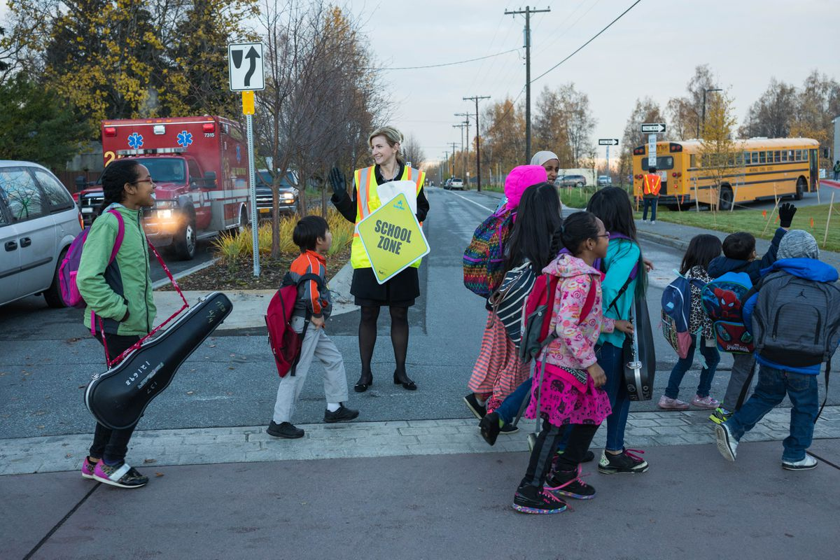 Anchorage School District superintendent Deena Bishop helps kids cross a street near Airport Heights Elementary School on International Walk to School Day, Wednesday, Oct. 5, 2016. (Loren Holmes / Alaska Dispatch News)