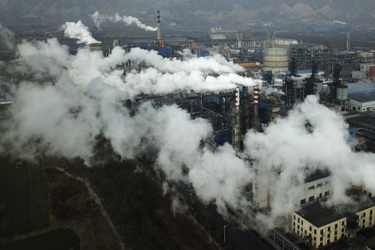 FILE - In this Nov. 28, 2019 file photo, smoke and steam rise from a coal processing plant that produces carbon black, an ingredient in steel manufacturing, in Hejin in central China's Shanxi Province. Scientists say greenhouse gas emissions must start dropping sharply as soon as possible to prevent global temperatures rising more than 1.5 degrees Celsius (2.7 degrees Fahrenheit) by the end of the century. So far, the world is on course for a 3- to 4-degree Celsius rise, with potentially dramatic consequences for many countries. (AP Photo/Sam McNeil, File)