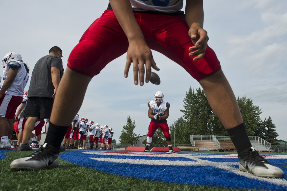 Isaako Manu, a senior, foreground, practices snapping the ball on Wednesday. (Marc Lester / ADN)