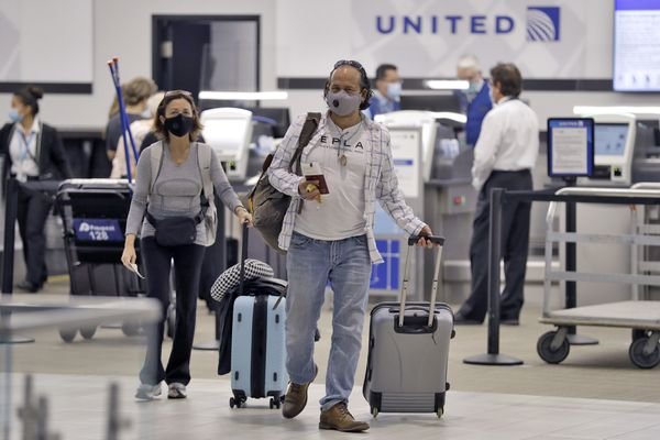 Passengers wearing personal protective face masks leave the United Airline ticket counter after checking in Tuesday, June 16, 2020, at the Tampa International Airport in Tampa, Fla. Some major US airlines, including United, American Airlines, Delta Air Lines, JetBlue, and Southwest Airlines, pledged to roll out new policies requiring masks for passengers to help stop the spread of the coronavirus. (AP Photo/Chris O'Meara)