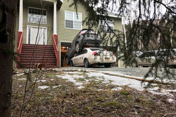 The Anchorage Police Department said a man who had barricaded himself inside and Eagle River home Friday tried to escape by backing out of his garage -- and into a police cruiser. The man was later taken into custody, police said. (Anchorage Police Department photo)