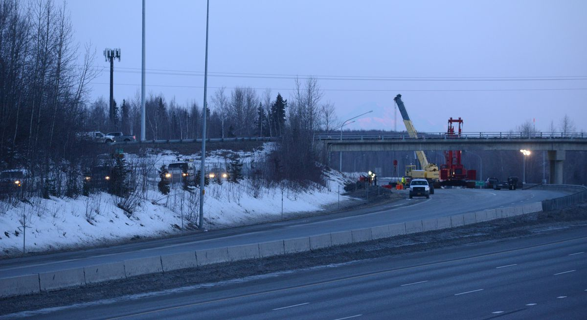 Traffic moves toward the new access to the Glenn Highway just past the South Eagle River overpass on Friday. Cranes are in position at the bridge as repair work starts. A truck transporting a modular building crashed into the interchange overpass on Wednesday, causing extensive damage. (Bob Hallinen / ADN)