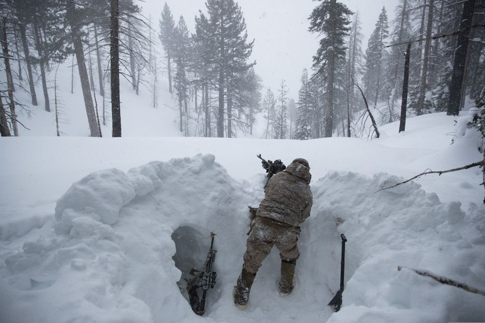 A U.S. Marine covers a machine gun in a trench while preparing for advanced cold-weather training at the Marine Corps Mountain Warfare Training Center Saturday, Feb. 9, 2019, in Bridgeport, Calif. After 17 years of war against Taliban and al-Qaida-linked insurgents, the military is shifting its focus to better prepare for great-power competition with Russia and China, and against unpredictable foes such as North Korea and Iran. (AP Photo/Jae C. Hong)