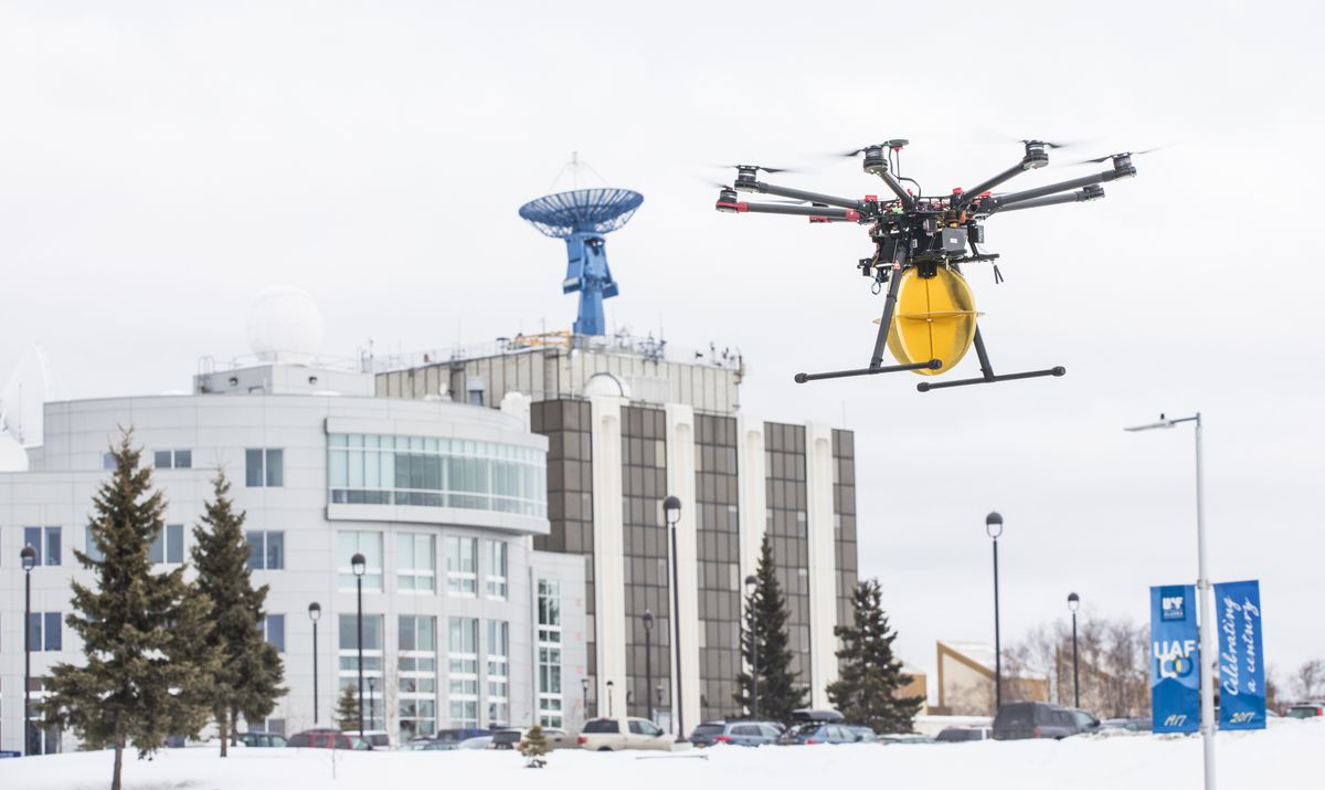 A Ptarmigan drone carrying a test payload flies in front of the UAF Geophysical Institute in Fairbanks on March 29, 2018. (JR Ancheta / UAF)