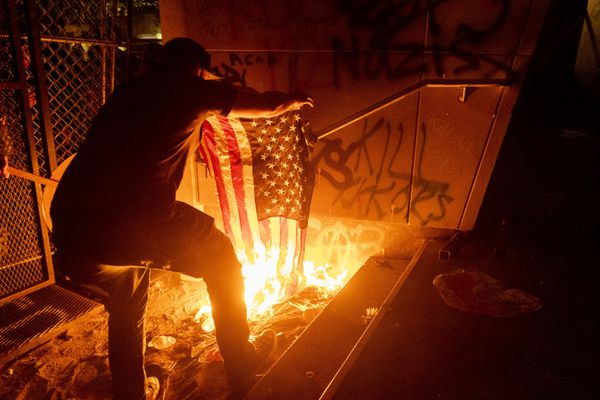 A Black Lives Matter protester burns an American flag outside the Mark O. Hatfield United States Courthouse on Monday, July 20, 2020, in Portland, Ore. Several hundred demonstrators gathered at the courthouse where federal officers deployed teargas and other crowd control munitions. (AP Photo/Noah Berger)