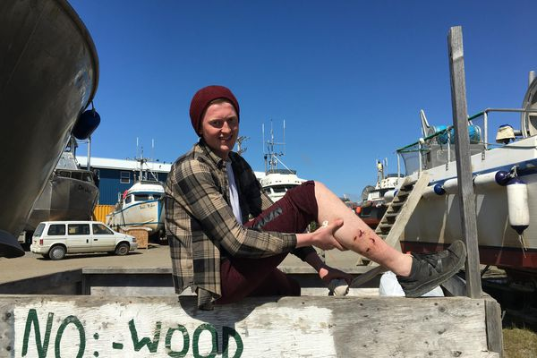 Nineteen-year-old Stig Ure poses for a photograph on the dumpster where he surprised a bear early on the morning of June 3, 2018, in the Upper Lummy boatyard in Naknek. (Mitch Borden / KDLG)
