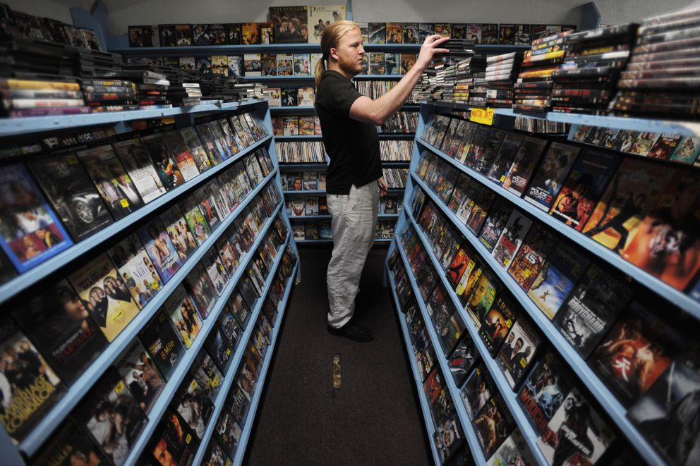 Jesse DeLaney purchased a stack of DVDs at Video City on Muldoon Road on Monday. (Bill Roth / Alaska Dispatch News)