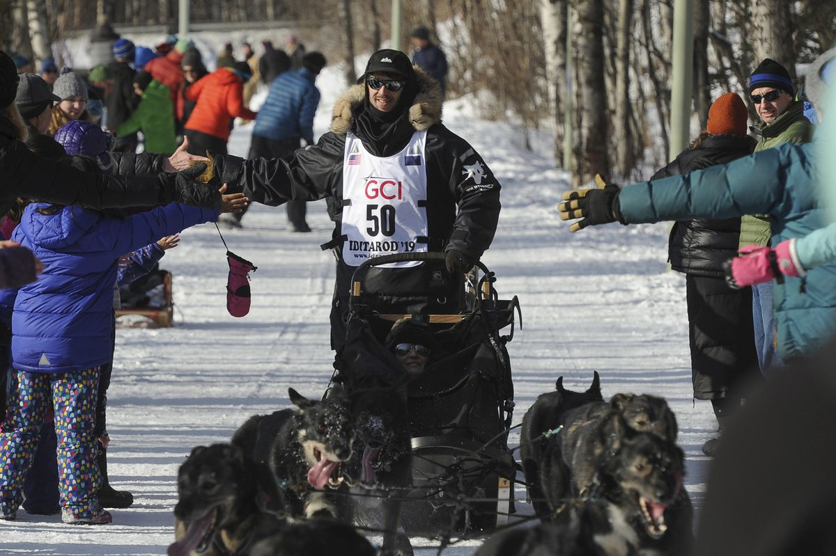 Iditarod rookie Richie Beattie greets fans on the trail during the ceremonial start of the Iditarod Trail Sled Dog Race, Saturday, March 2, 2019 in Anchorage, Alaska. (AP Photo/Michael Dinneen)