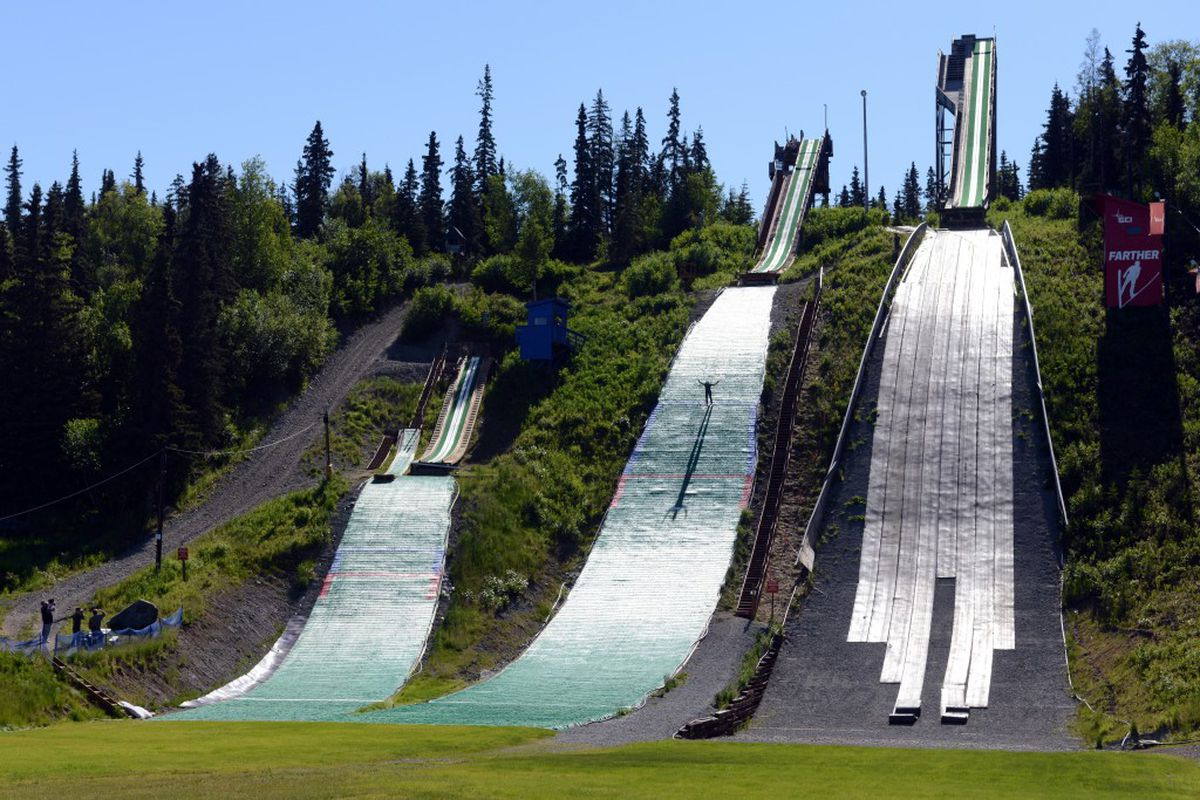 Gustavus Compton, 15, touches down during summer training on the 40-meter hill at the Karl Eid Ski Jumping Complex lastweek. The small-hill jumps at left are also ready to use, while prep work continues on the 65-meter hill at right. (Erik Hill / Alaska Dispatch News)
