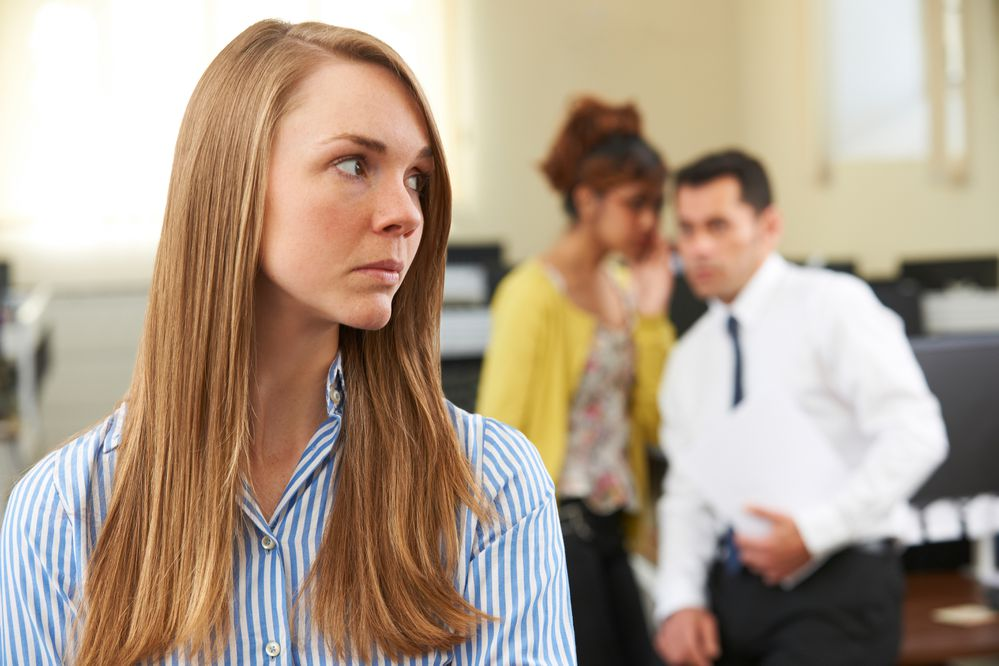 Businesswoman Being Gossiped About By Colleagues In Office (Getty Images)