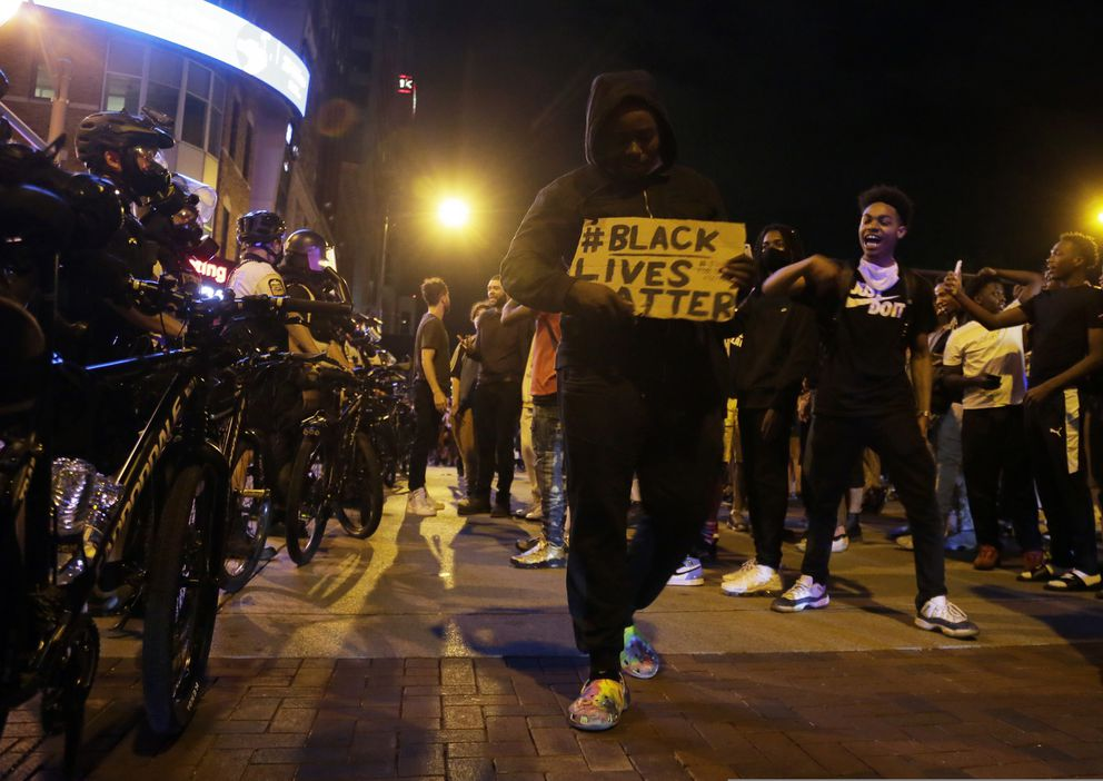 Protesters hold signs and walk past a line of police in downtown Columbus, Ohio, Thursday, May 28, 2020, during a demonstration over the death of George Floyd in police custody Monday in Minneapolis. Columbus police used pepper spray to disperse protesters after some threw plastic bottles of water, smoke bombs and other items at police. Windows at the Statehouse and in bus stations along High Street were shattered, trash cans were tossed and decorative planters wrecked. (Barbara J. Perenic/The Columbus Dispatch via AP)