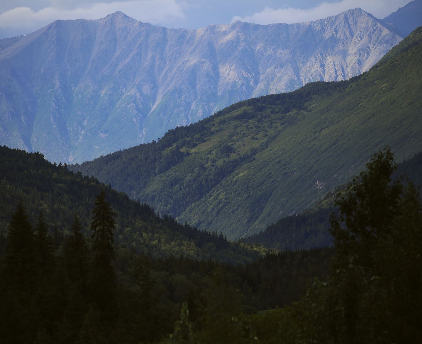 Sunlight casts shadows on layers of mountains along the Seward Highway on Aug. 9, 2020. (Emily Mesner / ADN)