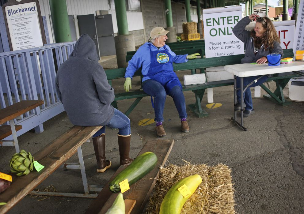 Deb Blaylock, center, talks with Kathy Liska, right, as they wait for people to enter vegetables into the Harvest Fest 2020. (Emily Mesner / ADN)
