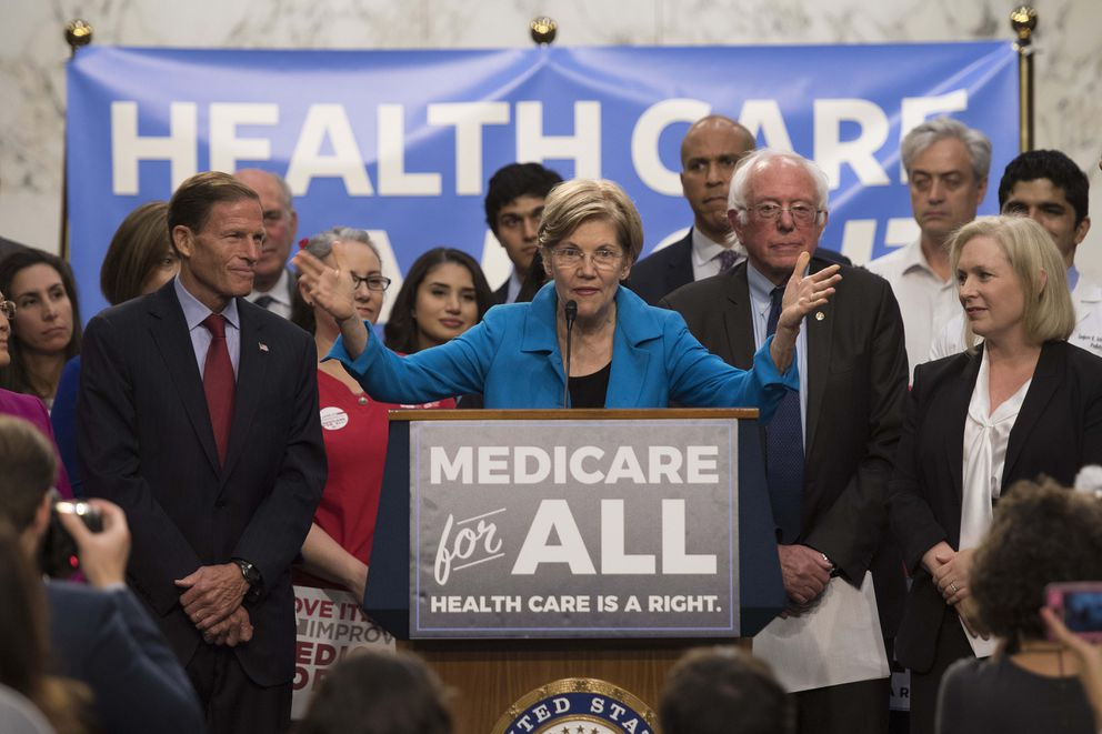 U.S. Sen. Elizabeth Warren, D-Mass., center, speaks with Sen. Bernie Sanders, I-Vt., second from right, as they discusses Medicare for All legislation on Capitol Hill in Washington, D.C., on September 13, 2017. (Jim Watson/AFP via Getty Images)