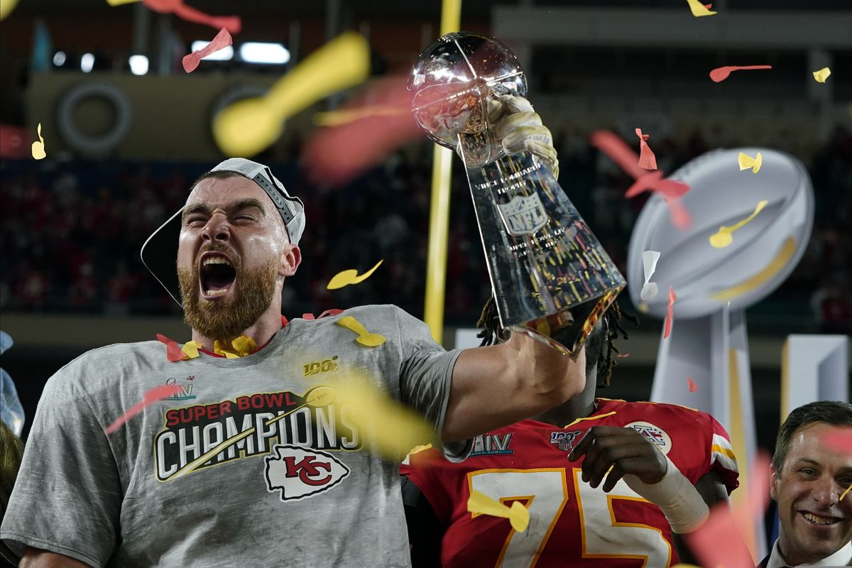 Kansas City Chiefs' Travis Kelce hoists the trophy after defeating the San Francisco 49ers in the NFL Super Bowl 54 football game Sunday, Feb. 2, 2020, in Miami Gardens, Fla. (AP Photo/David J. Phillip)
