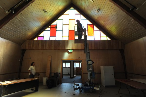 Alaska Housing Finance Corporation construction workers Dwayne Hansell, left, and Al Bert work on the ceiling of an old church purchased by the AHFC that is being used for community projects until it is demolished for new construction in their revitalization of Spenard on Thursday, July 14, 2016. (Bill Roth / Alaska Dispatch News)