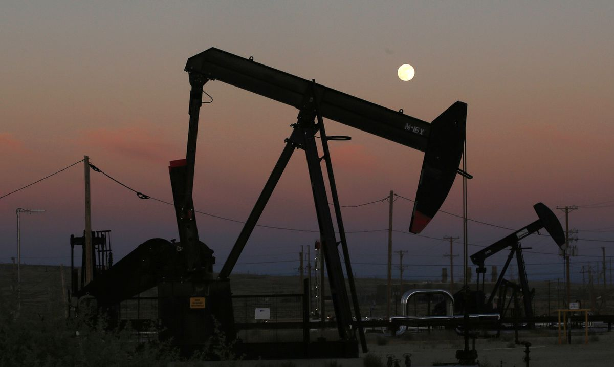 FILE - In this June 8, 2017, file photo, oil derricks are busy pumping as the moon rises near the La Paloma Generating Station in McKittrick, Calif. The U.S. is on pace to leapfrog both Saudi Arabia and Russia as the world's biggest oil producer. (AP Photo/Gary Kazanjian, File)
