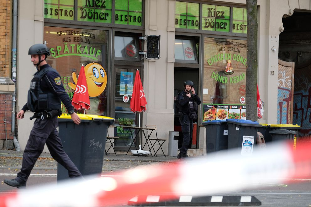 A police officer walks in front of a kebab grill in Halle, Germany, Wednesday, Oct. 9, 2019. A gunman fired several shots on Wednesday in the German city of Halle.(Sebastian Willnow/dpa via AP)