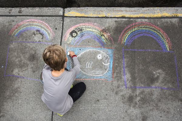 Christian Laird, 8, draws a halibut using chalk as part of the
