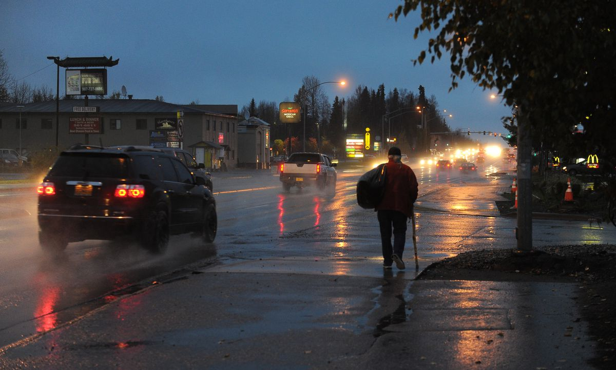 With his sleeping bag over his shoulder, Doug Shepard walks away from the Anchorage Gospel Rescue Mission along Tudor Road in Anchorage. Shepard, who is homeless, has timed out at the mission. (Bob Hallinen / Alaska Dispatch News)
