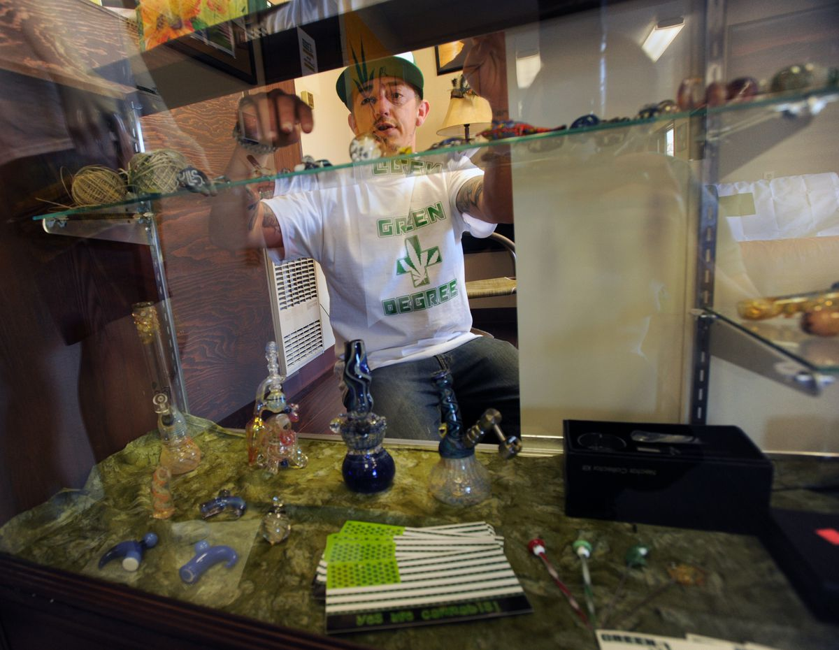Jesse DeMarco Mazzella retrieves a glass item from a display case in the Green Degree reception area near Wasilla. An expanded retail area is being set up in an adjacent, larger room. (Erik Hill / Alaska Dispatch News)
