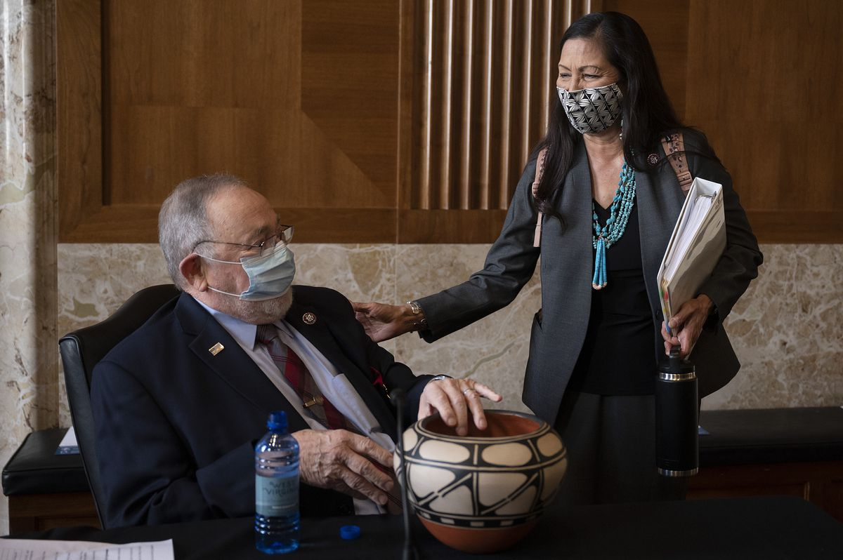Rep. Deb Haaland, D-N.M., delivers a gift to Rep. Don Young, R-Alaska, before the start of the Senate Committee on Energy and Natural Resources hearing on her nomination to be Interior Secretary, Tuesday, Feb. 23, 2021 on Capitol Hill in Washington. (Jim Watson/Pool via AP
