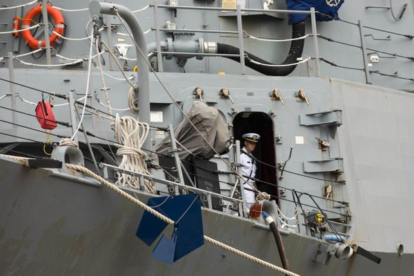 A crew member looks out from a door aboard the guided-missile destroyer USS Momsen as it is docked at the Port of Alaska on Wednesday, Aug. 15, 2018. (Loren Holmes / ADN)