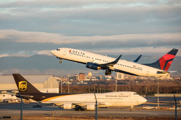 A Delta Airlines plane takes off while a UPS cargo plane taxies to the runway on Thursday, Nov. 17, 2016 at Ted Stevens Anchorage International Airport. (Loren Holmes / Alaska Dispatch News)