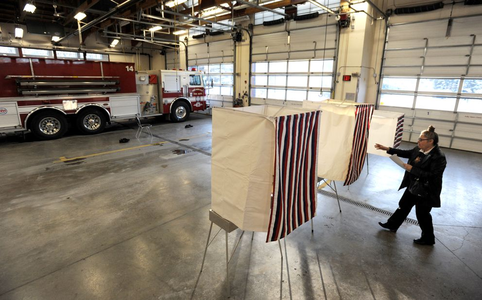 Ellen Harness reaches for a voting booth curtain while voting at AFD Station 14 on Election Day, Tuesday, Nov. 6, 2018. (Bill Roth / ADN)