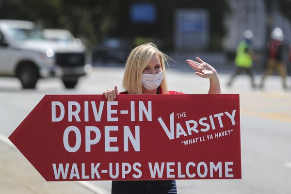Ashley Weiser, the great granddaughter of The Varsity founder Frank Gordy, wearing a face mask holds a sign Tuesday, April 28, 2020 at 61 North Ave NW in downtown Atlanta. All the Varsity locations are open with limited hours for drive-thru and drive-in only service and are accepting only debit and credit cards. The restaurant is assuring customers they are following the guidelines from the CDC and Governor's office during the COVID-19 pandemic. (John Spink/Atlanta Journal-Constitution via AP)