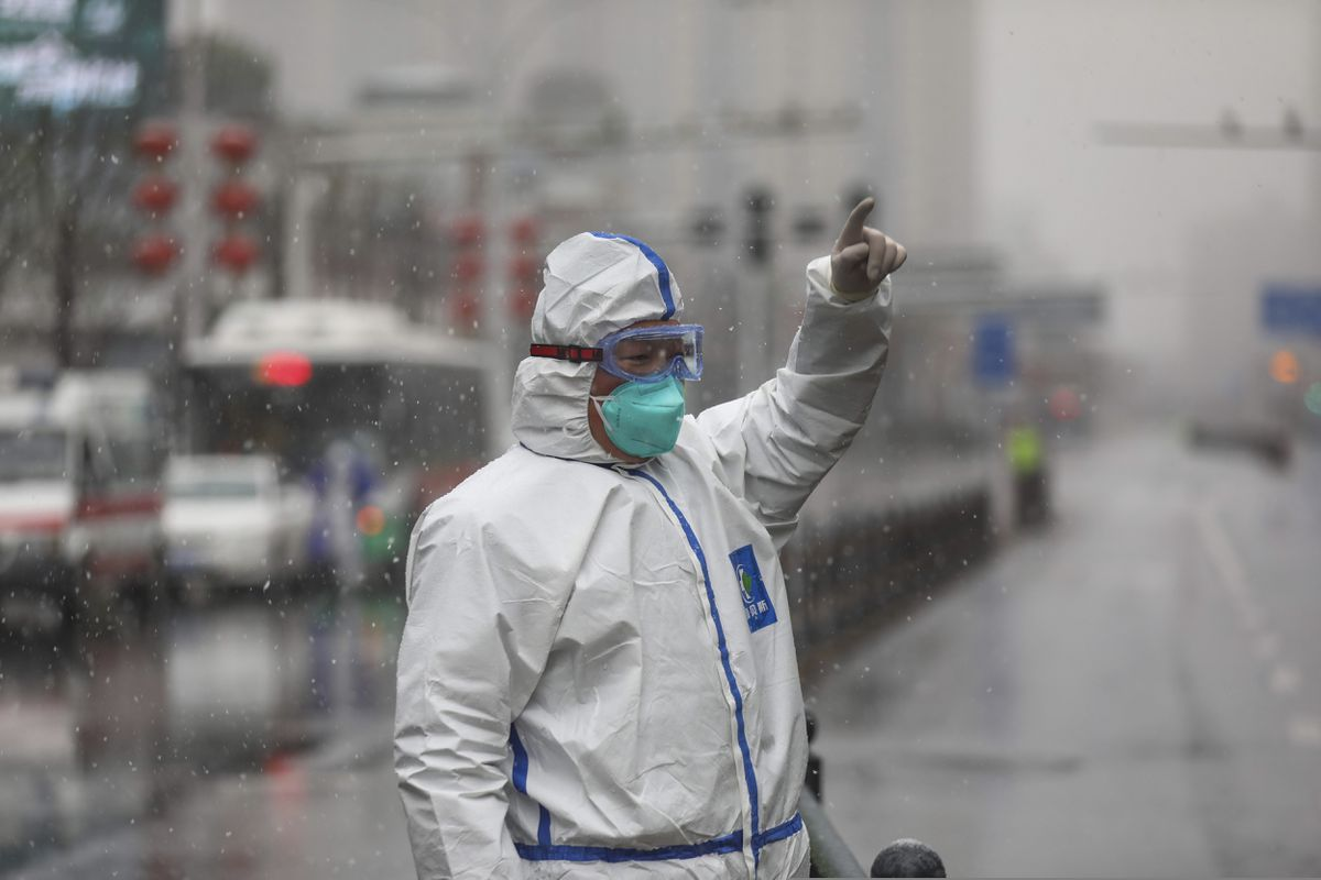 A worker wearing a protective suit gestures to a driver outside a tumor hospital newly designated to treat COVID-19 patients in Wuhan in central China's Hubei Province, Saturday, Feb. 15, 2020. (Chinatopix via AP)