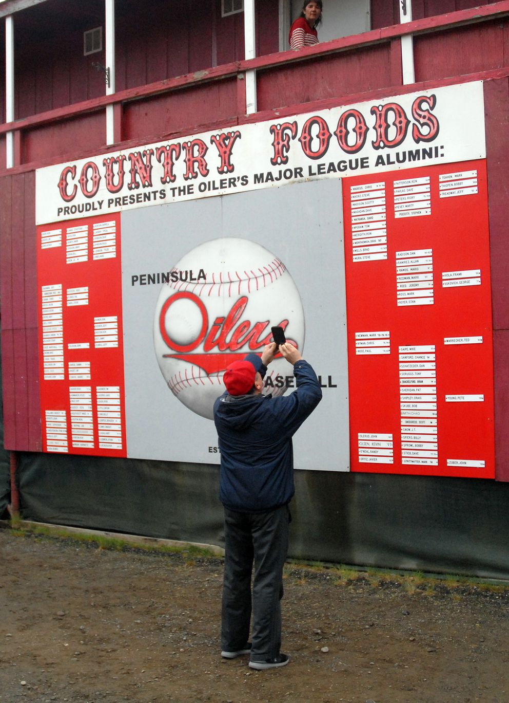 Chinooks booster club president Tim Barto photographs a list of Peninsula Oilers who went on to play Major League Baseball. (Matt Tunseth / Chugiak-Eagle River Star)
