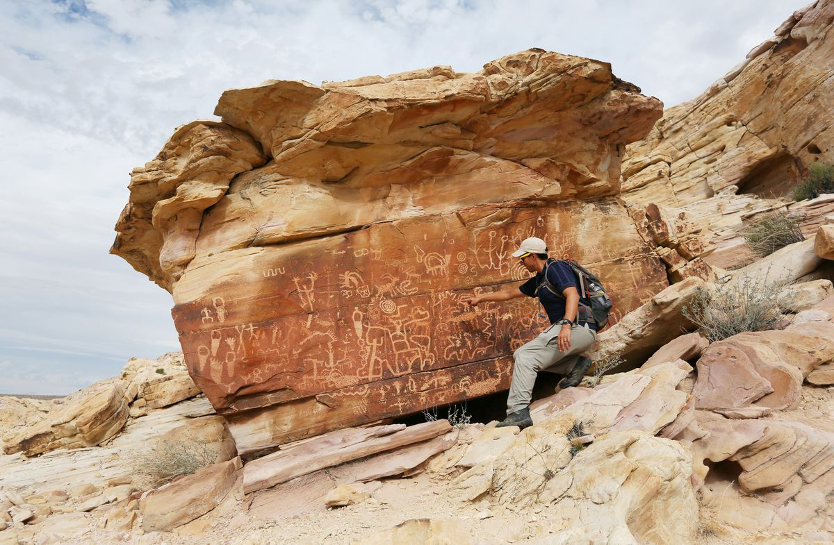 Jose Witt, Southern Nevada director of Friends of Nevada Wilderness, points out petroglyphs while leading a hike this fall in Gold Butte. The area is now one of the newest national monuments. (Photo for The Washington Post by Ronda Churchill)