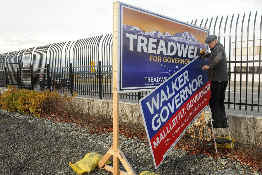 Bob Walker, the older brother of Governor Bill Walker takes down Walker campaign signs at Merrill Field in Anchorage, AK on Saturday, Oct 20, 2018. The Walker campaign had taken over the Mead Treadwell sign stand after Treadwell ended his campaign for governor. Walker also removed the Treadwell signs. (Bob Hallinen / ADN)