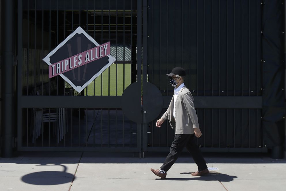 In his photo taken June 25, 2020, man wears a face mask during the coronavirus outbreak while walking past partially covered fencing outside Oracle Park, the San Francisco Giants' baseball ballpark, in San Francisco. This week, Major League Baseball players and owners reached an agreement to play an abbreviated, 60-game season that would start July 23 or 24 in teams' home ballparks. But the seats will be empty. Instead, fans hoping to see a game in person will be have to settle for pressing their faces up against hotel windows, squinting through metal grates or climb to rooftops when baseball returns this month in otherwise empty stadiums. (AP Photo/Jeff Chiu)
