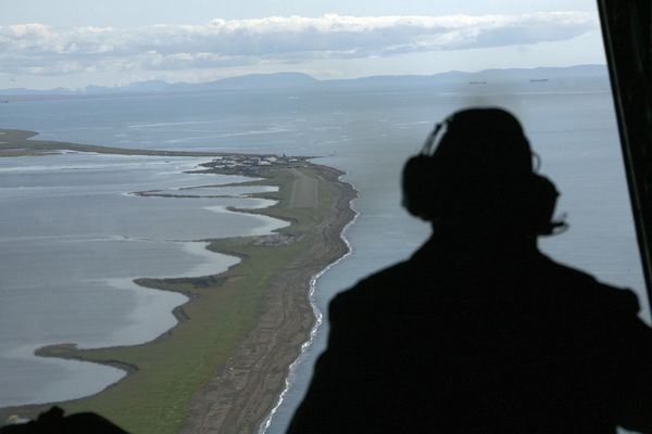 FILE - In this Aug. 7, 2008, file photo, Aviation Maintenance Tech 2, John Ferrari looks out of the back of a U.S. Coast Guard C-130 as he surveys the coast near the village of Kivalina, Alaska, during a surveillance flight to the Arctic. Northern Alaska coastal communities and climate scientists say sea ice disappeared far earlier than normal this spring, and it's affecting wildlife. The Anchorage Daily News reported in June 2019 that ice melted because of exceptionally warm ocean temperatures. (AP Photo/Al Grillo, File)
