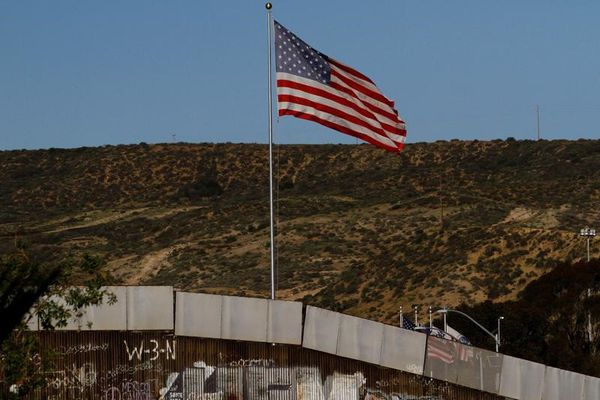 A U.S. flag is seen next to a section of the wall separating Mexico and the United States, in Tijuana, Mexico, January 28, 2017. REUTERS/Jorge Duenes