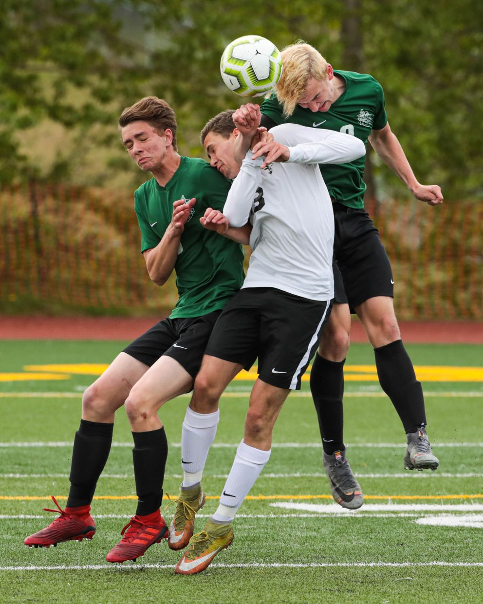 From left, Colony's Michael Silwa, West's Ben Bruen, and Colony's Noah Krozel all try to head the ball Saturday, May 25, 2019 during the state high school soccer match at Service High. (Loren Holmes / ADN)