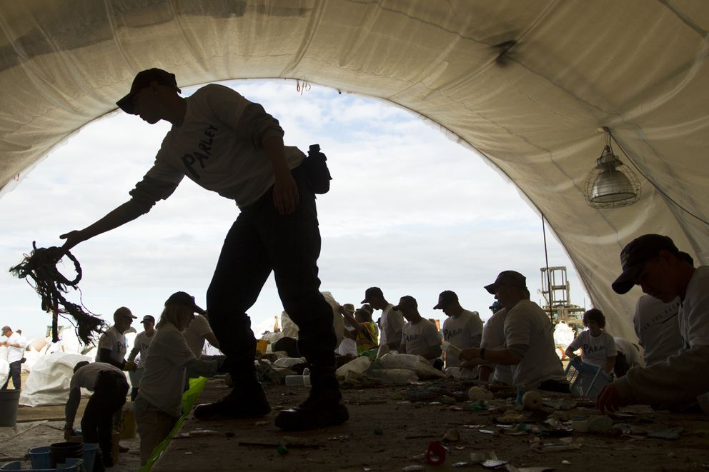 Jacob Endicott tosses rope into a pile while sorting debris found in the Pacific Ocean during the Great Alaska Marine Debris Sorting Project at the Port of Anchorage on Saturday, July 16, 2016. Volunteers sorted plastics, netting and buoys. (Sarah Bell / Alaska Dispatch News)