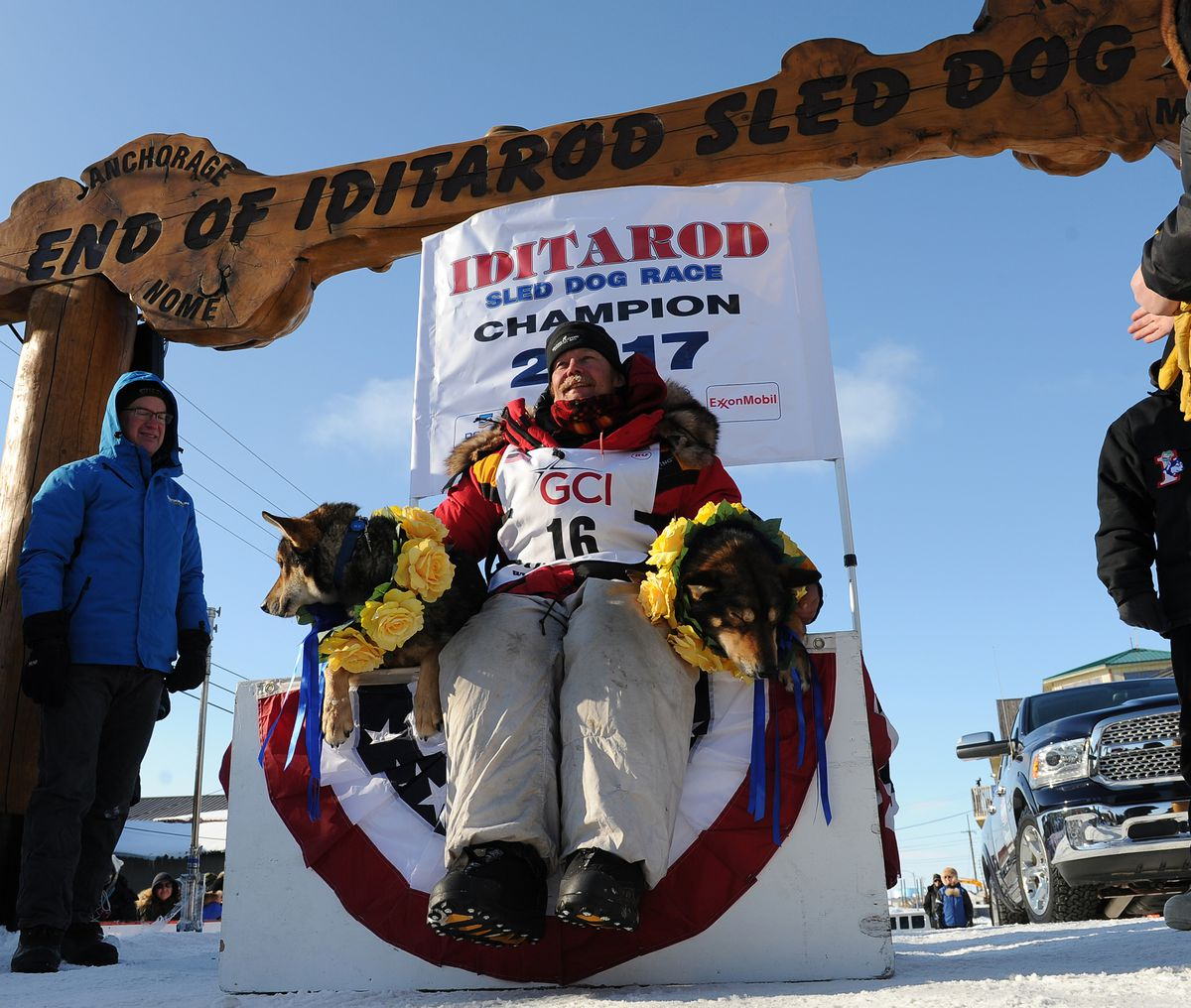 Mitch Seavey and lead dogs Pilot and Crisp sit under the burled arch in Nome after winning the 2017 Iditarod Trail Sled Dog Race. (Bob Hallinen / ADN)