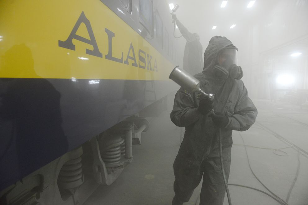 Joe Freel, on the ladder, puts a clear coat on the side of an Alaska Railroad passenger car as Ken Orr heads out to refill his spray gun at Ship Creek in Anchorage on Friday, April 13, 2018. Alaska Industrial Paint has a contract to paint Alaska Railroad cars. The cars used to be shipped to the Lower 48 to be painted. (Bob Hallinen / ADN)