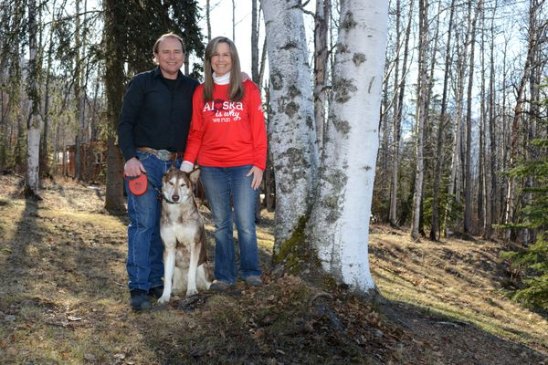 Keith and Jodi Herte and their dog Kiska pose in the yard of their Eagle River home at the spot Jodi suffered cardiac arrest in May of 2014. Keith saw Jodi down on the ground and saved her life by performing hands-only CPR until help arrived. Jodi was planning to run the 2017 Alaska Heart Run until a Tuesday evening fall while walking Kiska resulted in a broken hand. She still plans to walk the event. (Erik Hill / Alaska Dispatch News)