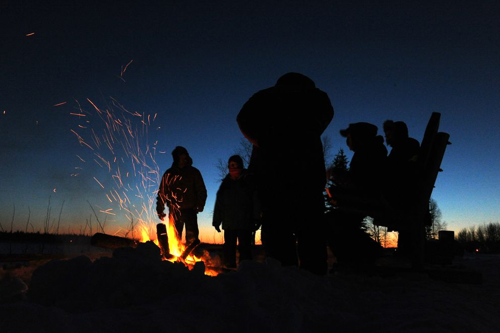 Village residents gather around a fire as mushers start to come in at the checkpoint in Tanana on Tuesday. (Bob Hallinen / Alaska Dispatch News)