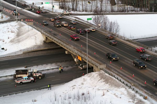 Crews work on the damaged Tudor Road overpass Thursday morning Jan. 3, 2019. The Seward Highway was closed for a few hours after a truck struck the bridge. (Loren Holmes / ADN)