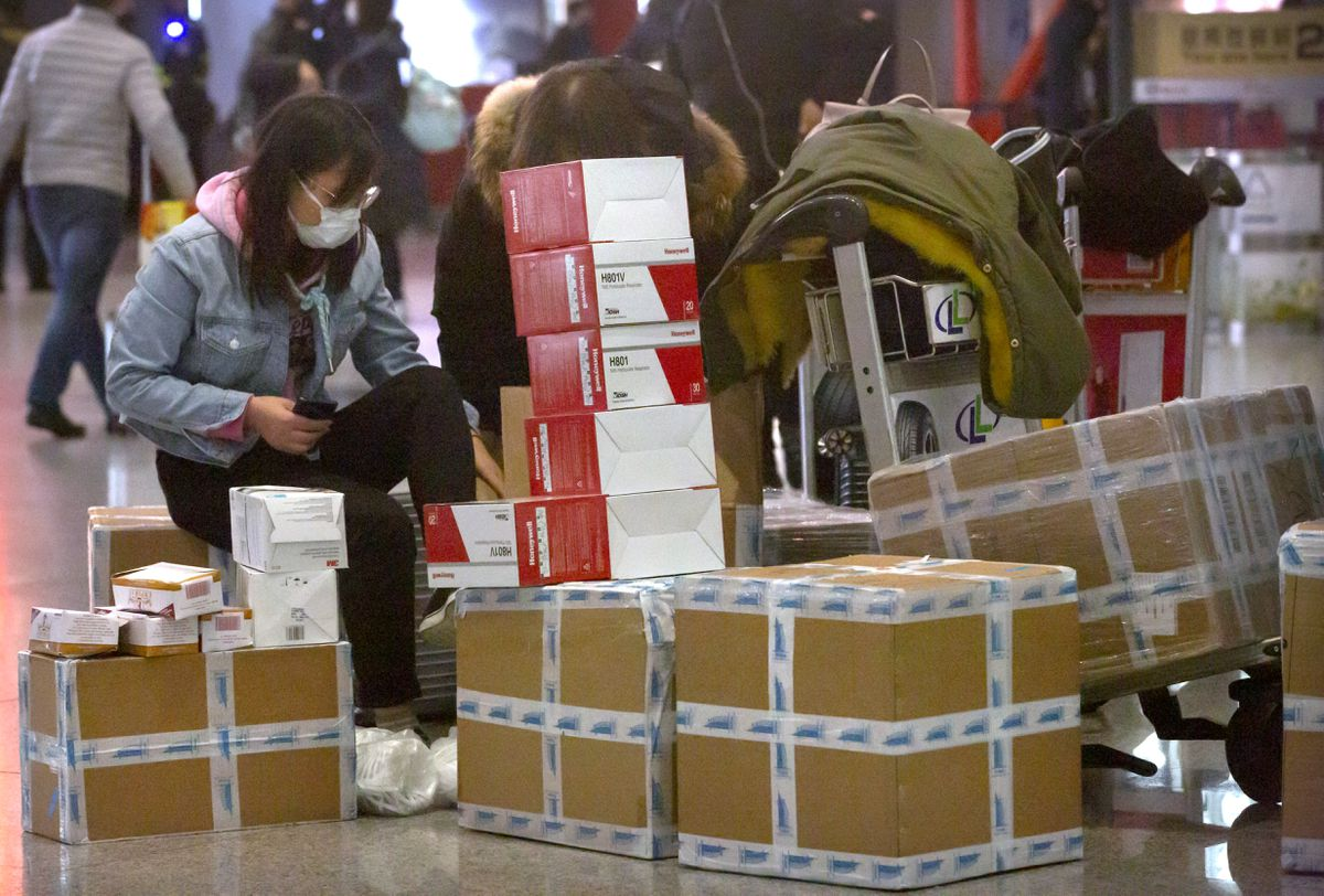 A traveler sits near boxes of face masks and respirators at the Beijing Capital International Airport in Beijing, Thursday, Jan. 30, 2020. China counted 170 deaths from a new virus Thursday and more countries reported infections, including some spread locally, as foreign evacuees from China's worst-hit region returned home to medical observation and even isolation. (AP Photo/Mark Schiefelbein)