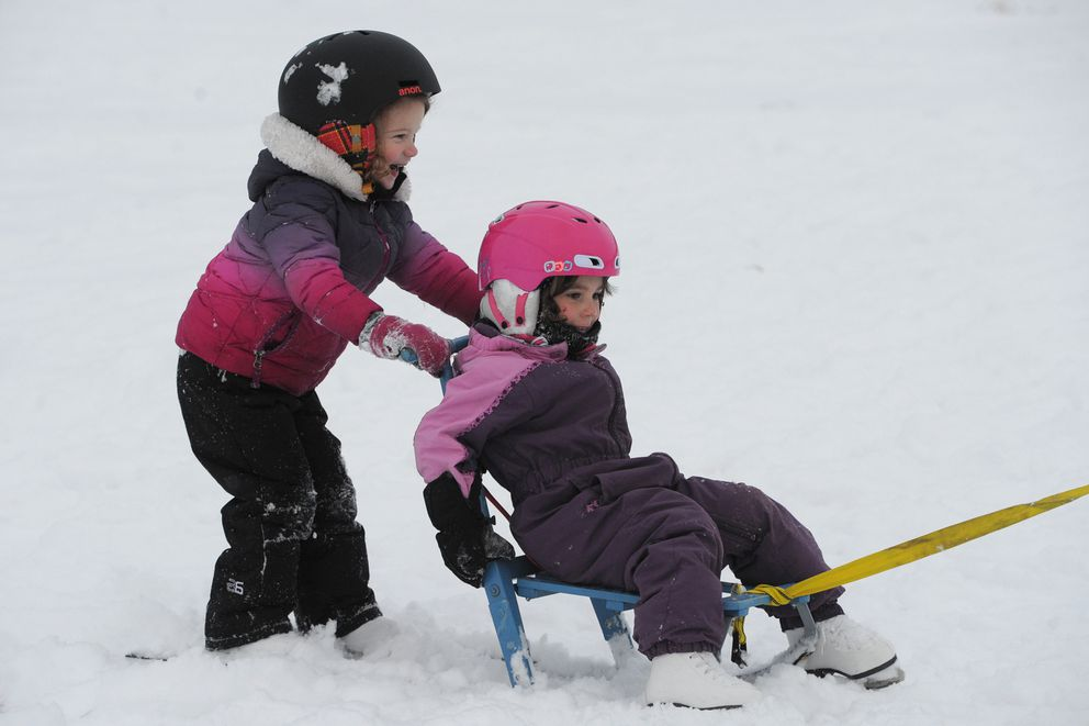 Emerson Schut and Daphne Pasch, both 4, ride a kick sled while ice skating on a snow-covered Westchester Lagoon on Christmas Day, Dec. 25, 2019. (Bill Roth / ADN)